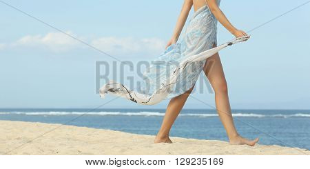 Girl walking on the beach - only legs