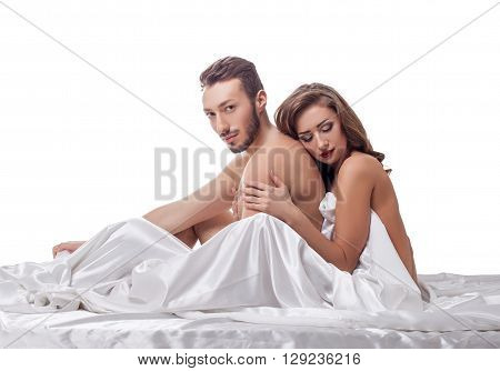 Erotica. Loving couple posing in bed, isolated on white