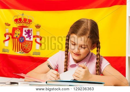 Diligent teenage student, Caucasian girl, writing with a pen in her copybook, Spanish flag behind