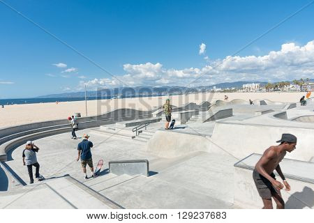 October 6, 2015 Venice Beach, USA Black male with cap on reverse blurred as he skates out of frame in skate bowl