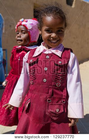 ASWAN, EGYPT - FEBRUARY 7, 2016: Cute local girls on street of Nubian village on the Nile.