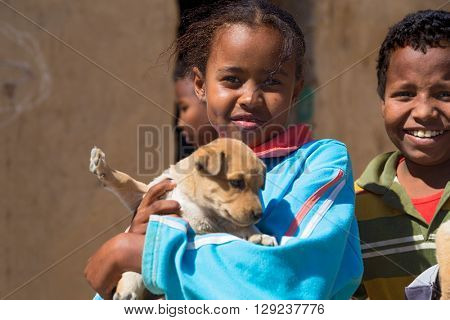 ASWAN, EGYPT - FEBRUARY 7, 2016: Local girl holding puppy in Nubian village on the Nile posing for camera.