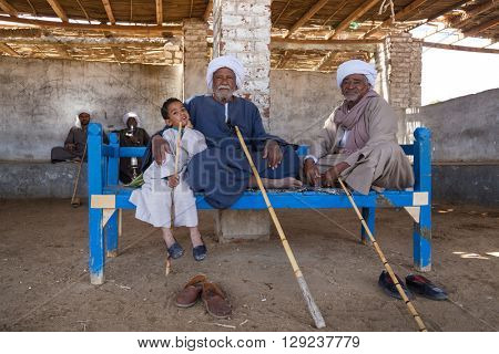 DARAW, EGYPT - FEBRUARY 6, 2016: Two elderly camel salesmen and little boy sitting on the bench at Camel market.