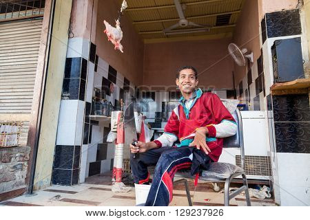 DARAW, EGYPT - FEBRUARY 6, 2016: Young local butcher sitting on the chair holding knife in front of butcher shop.