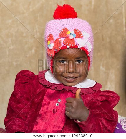 NUBIAN VILLAGE, EGYPT - FEBRUARY 7, 2016: Portrait of cute Nubian little girl in traditional clothes showing thumb up.