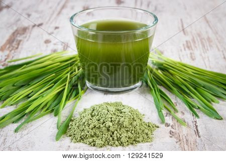 Heap of young powder barley barley grass and beverage on old rustic wooden background healthy nutrition and lifestyle body detox