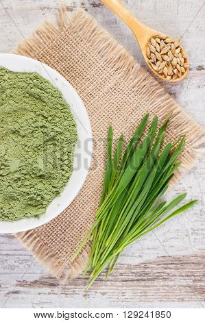 Young powder barley in bowl barley grass and grain on jute canvas old wooden background healthy nutrition and lifestyle body detox