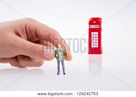 Hand holding a figure near a phone booth on a white background