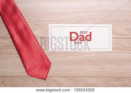 Fathers day composition with greeting card and colorful tie on wooden desk background.