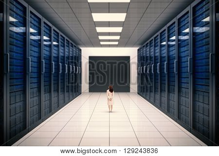 Rear view of businesswoman against server room with towers