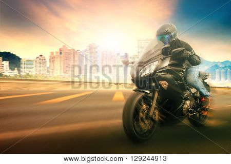 younger man wearing safety helmet and riding suit biking sport motorcycle on urban road with blurry background use for people traveling and sport activityleisure