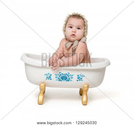 little baby in hat sitiing in a little bath isolated on white background