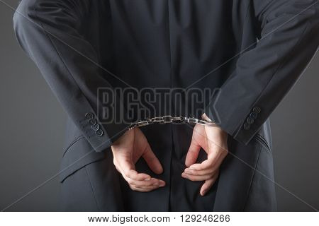 businessman in handcuffs arrested isolated on grey background
