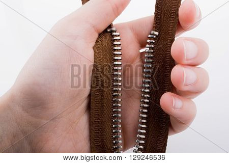 Hand holding color zipper on a white background