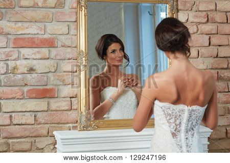 Beautiful happy bride looking at herself in mirror.