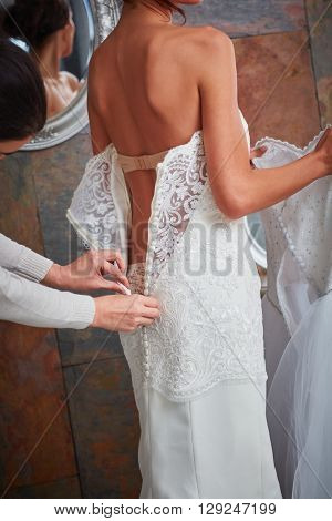 Female friend fastening buttons on wedding dress, photographed from behind.