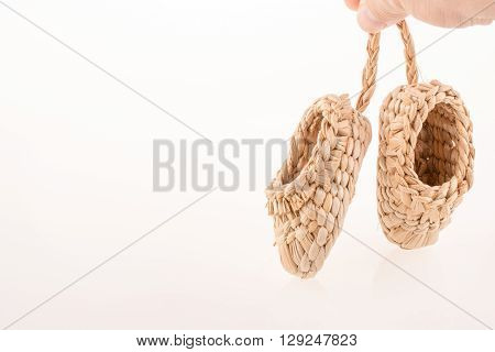 Pair of footware made of straw on white background
