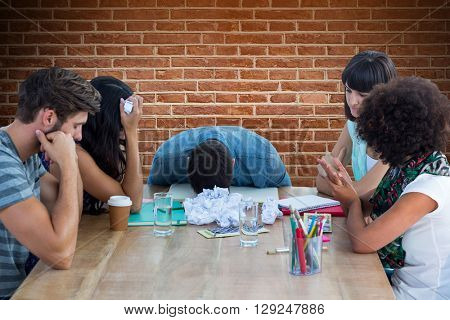 Exhausted creative business team in meeting against red brick wall