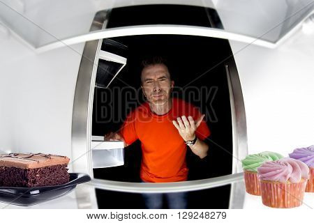 Hungry man looking in fridge for sweet dessert or junk foods