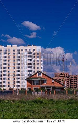 The construction of large apartment buildings displaces small homes. City absorbs the village.