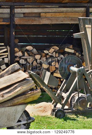 Circular saw with wood logs and log store in garden. Woodworking in garden.