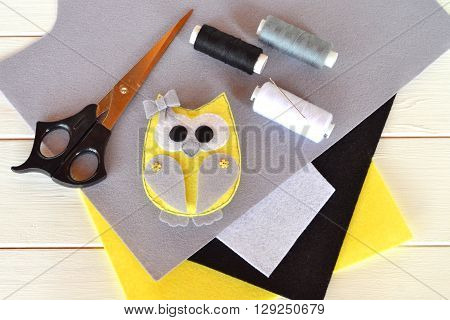 Felt owl toy. Animal owl. Felt sheets, scissors, thread, needle, pins - a set for needlework. Wooden background.