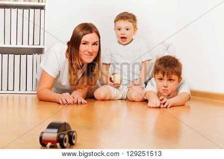 Mother and her two sons playing with toy wooden car laying at the floor