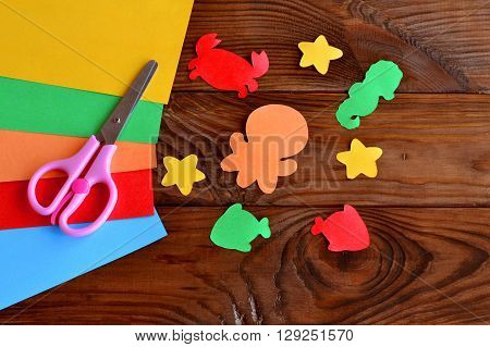 Paper sea animals - octopus, fish, starfish, seahorse, crab. Children's paper crafts. Kids diy. Sheets of colored paper, scissors on wooden background