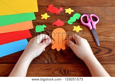 Paper sea animals - octopus, fish, starfish, seahorse, crab. Child holds a paper octopus in hands. Kids diy. Sheets of colored paper, scissors on wooden background