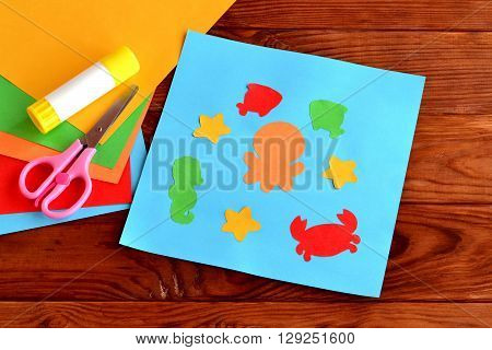 Sea animal and fish DIY Crafts Project Ideas for Kids. Children's paper crafts. Sheets of colored paper, scissors, glue on wooden background. Card with paper marine inhabitants