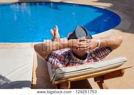 man in hat sunbathing on a sun lounger by the pool.