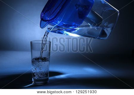 Filter jug pouring water in the glass, on dark background