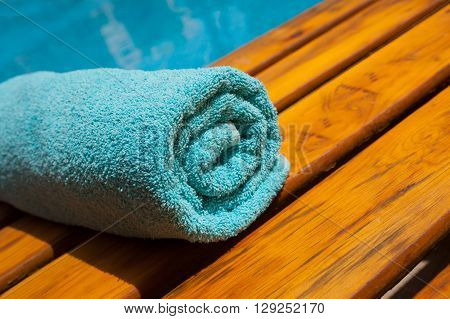 turquoise towel on a lounger by the blue pool.
