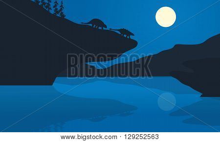 Silhouette of ankylosaurus at the night in cliff