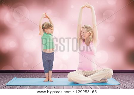 Pregnant smiling mother and daughter doing yoga together against orange abstract light spot design