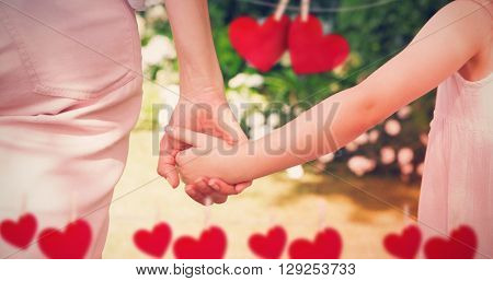 Composite image of close up of mother and daughter holding hands each other with heart tinsel
