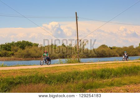 GRADO ITALY - APRIL 25: Little brother and sister cycling in the Nature reserve of the Isonzo river mouth on April 25 2016