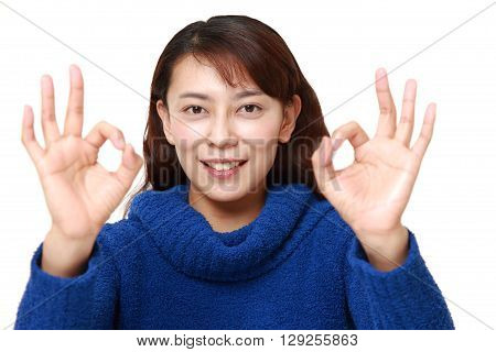 portrait of Asian woman showing perfect sign on white background