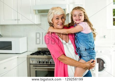 Portrait of smiling granny carrying girl while standing in kitchen