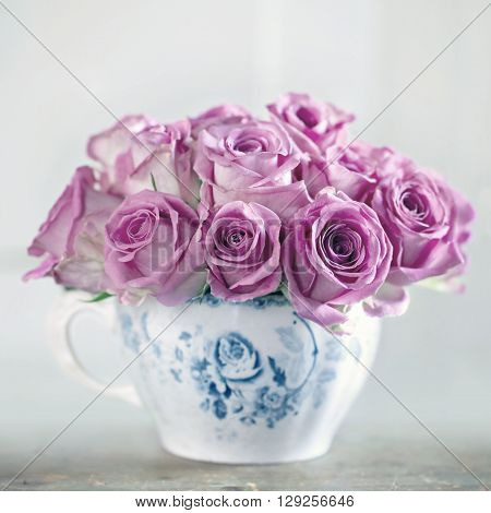 Bouquet of roses in an old cup on vintage wooden backgrond