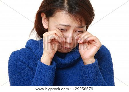 portrait of Asian woman with crocodile tears on white background