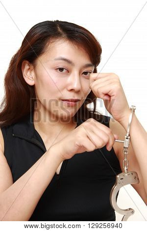 studio shot of woman with unlocked handcuffs