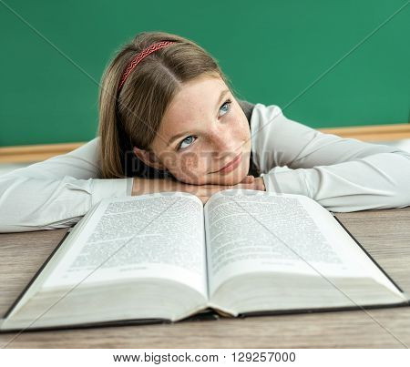 Fantasy pupil looking up as if daydreaming or thinking of something pleasant while sitting at the desk with open book. Photo of teen school girl creative concept with Back to school theme