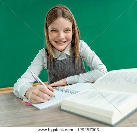Happy joyful teenage girl teaches homework. Photo of teen school girl creative concept with Back to school theme