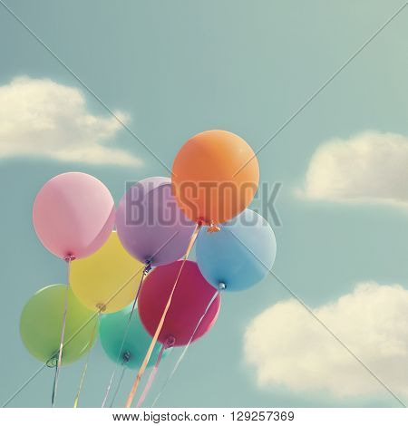 Bunch of colorful balloons on a blue sky with vintage editing