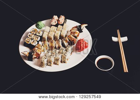 Japanese food restaurant, sushi maki unagi gunkan roll plate or platter set. Chopsticks, ginger, soy sauce and wasabi. Sushi at white round plate, black background.