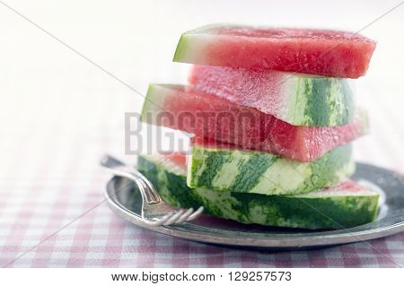 Plate full of watermelon on chequered table cloth with creamy vintage editing