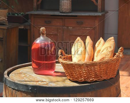 The picture shows a bottle of red wine standing on a barrel. Nearby lies a wicker basket with fresh bread.