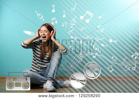 Young woman sitting on floor, listening to music and signing loud against blue wall