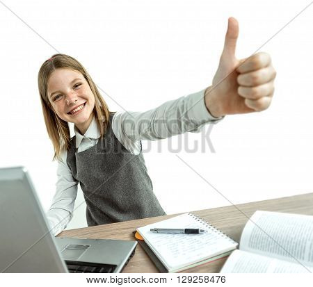Happy smiling young girl showing thumbs up gesture while using her laptop computer. Photo of teen school girl creative concept with Back to school theme